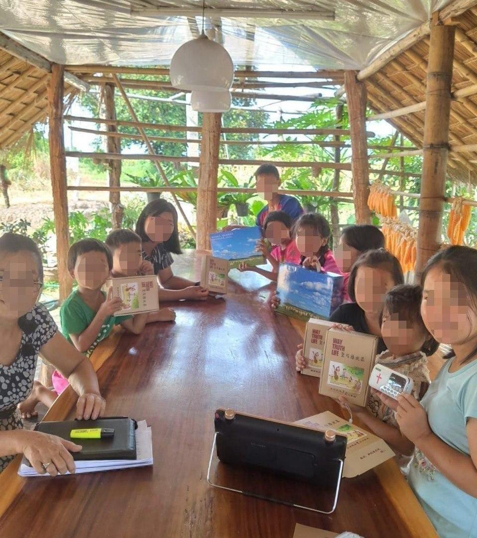 Kiinan syrjäseudulla asuvat lapset tutustumassa paketin sisältöön.